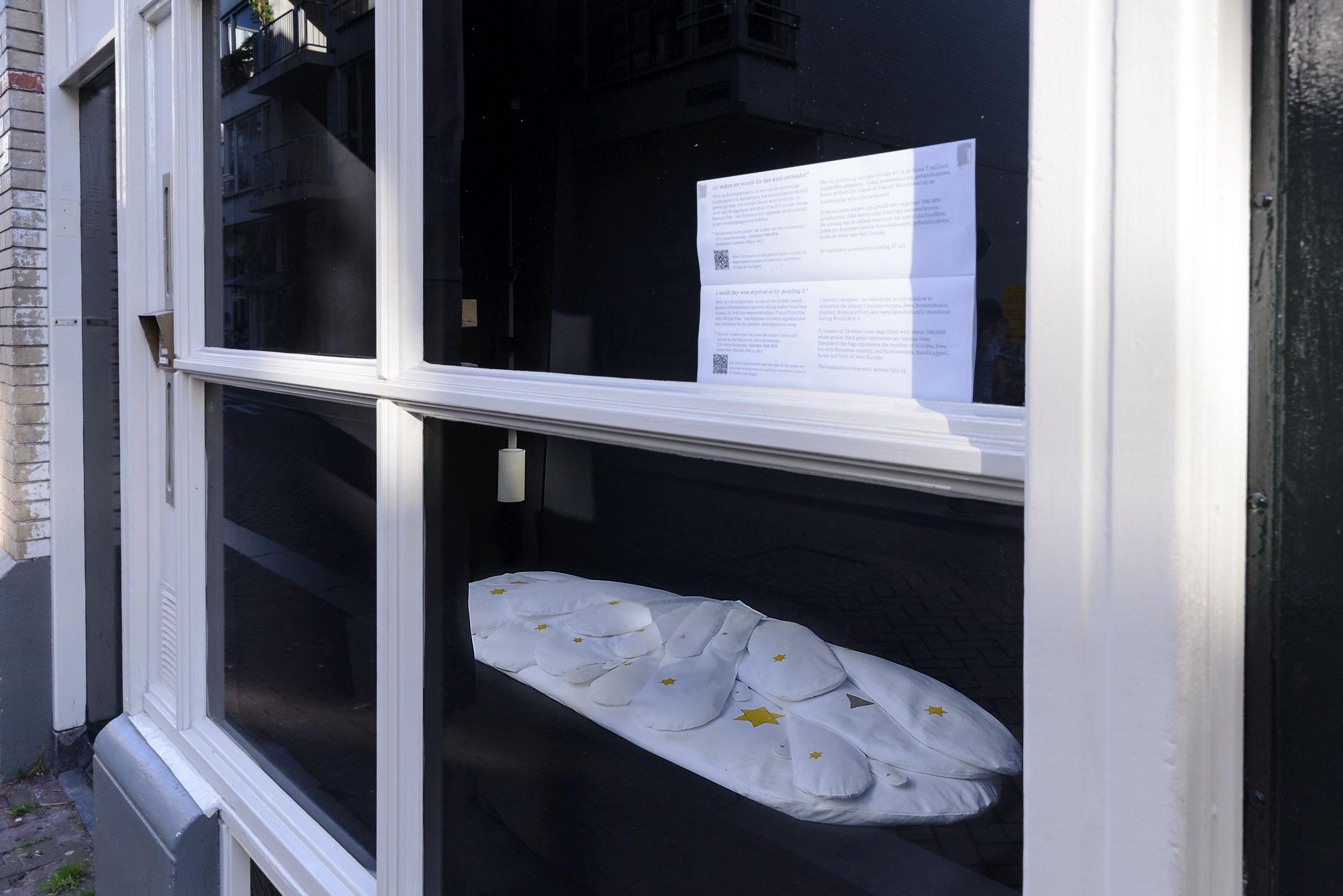 Gedenkinstallatie Koningsstraat 6, Amsterdam. Achter het venster liggen op een baar 23 witte linnen zakken gevuld met tarwekorrels.